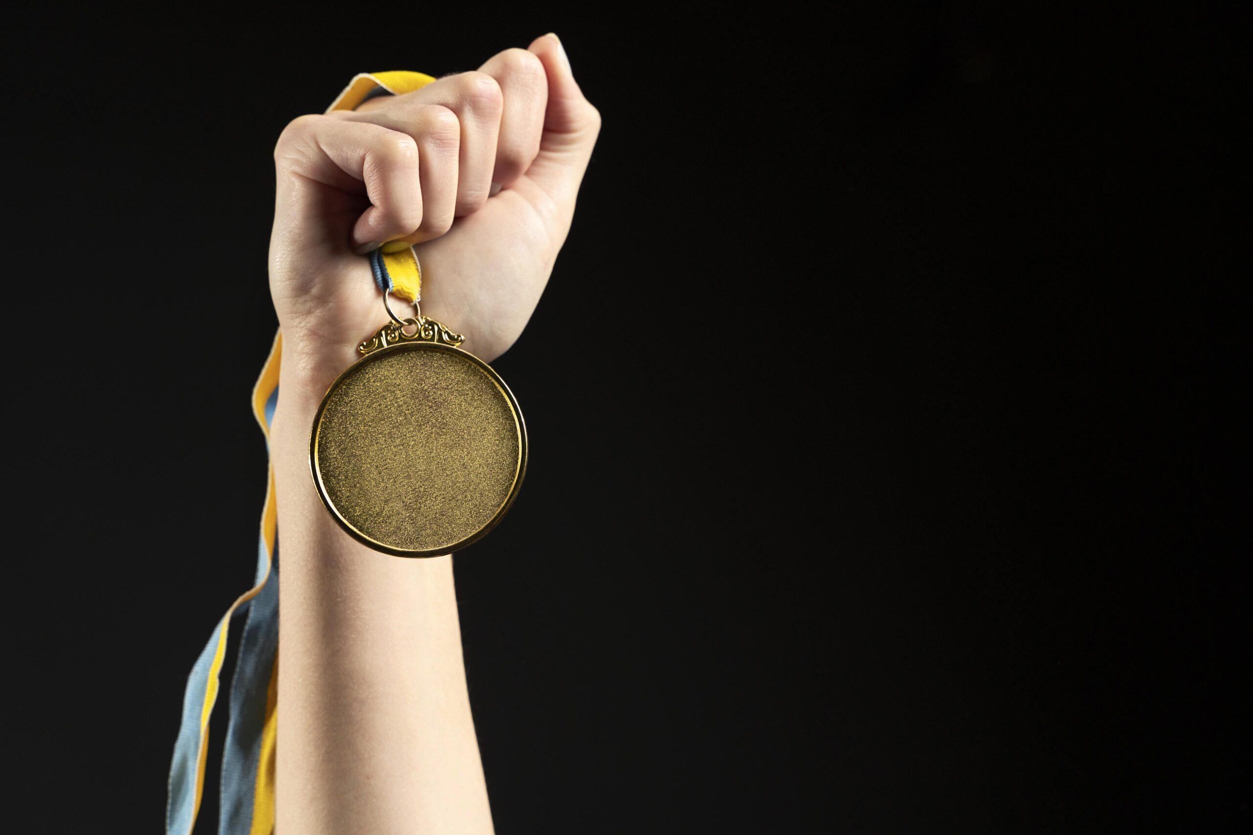 Mano sosteniendo una medalla de oro